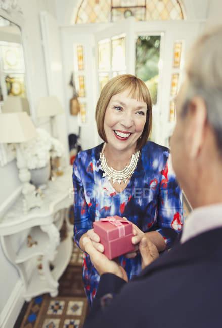 Sonriente mujer madura recibiendo regalo de marido - foto de stock