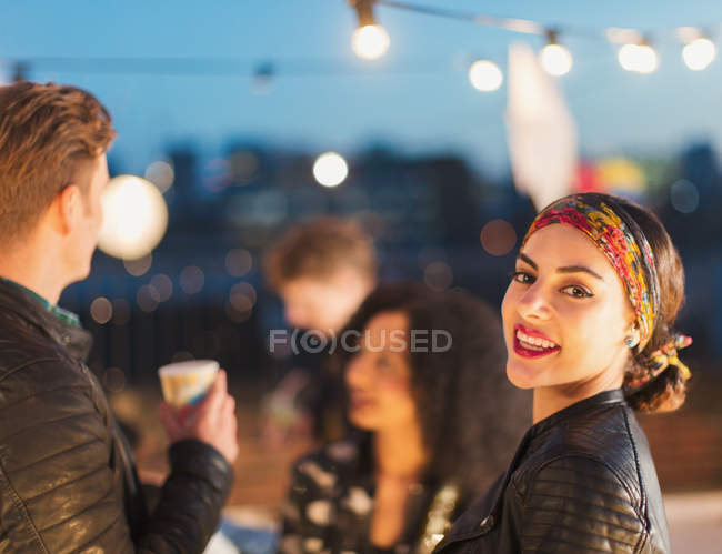 Portrait smiling young woman enjoying rooftop party at night — Stock Photo