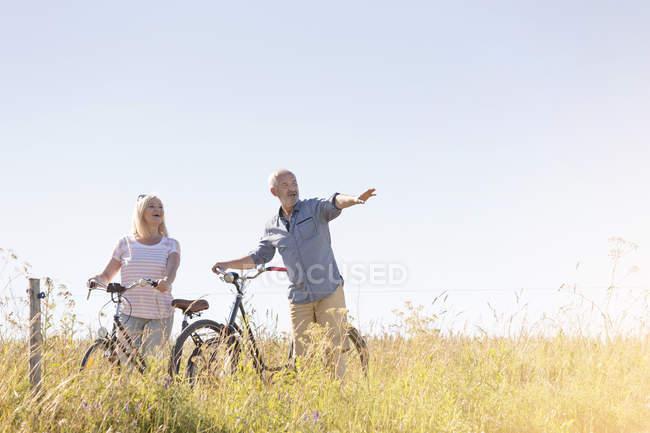 Älteres Paar Fahrrad fahren auf sonnigen ländlichen Gebiet unter blauem Himmel — Stockfoto