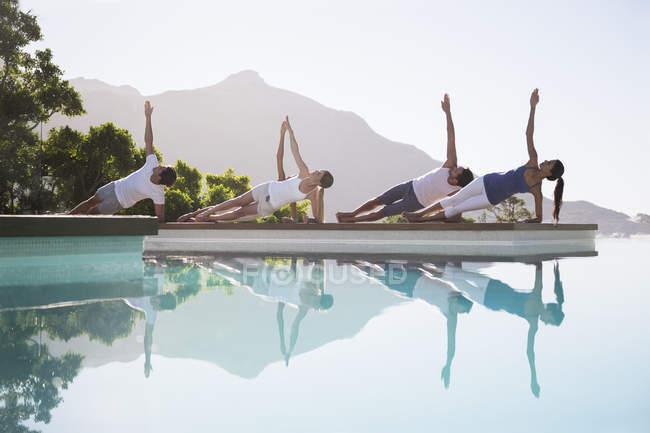 Молодые привлекательные люди практикующие йогу у бассейна — стоковое фото