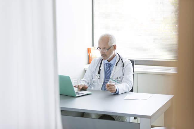 Doutor trabalhando no laptop no consultório do médico — Fotografia de Stock