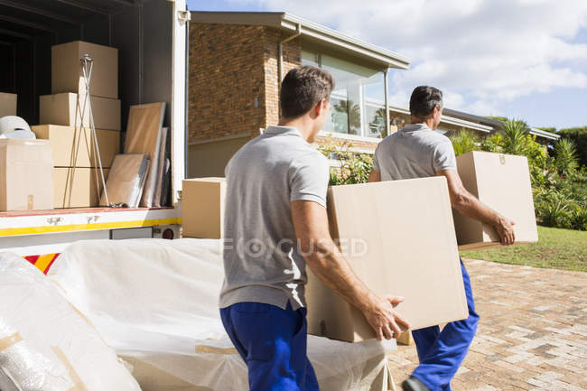 Movers carrying boxes in new house — Stock Photo