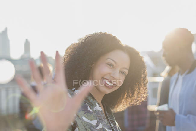 Portrait smiling woman waving at rooftop party — Stockfoto