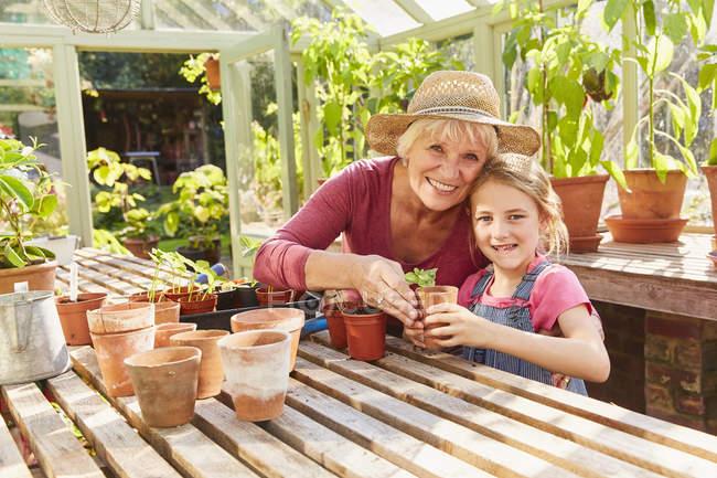 Porträt lächelnde Großmutter und Enkelin Topfpflanzen im Gewächshaus — Stockfoto
