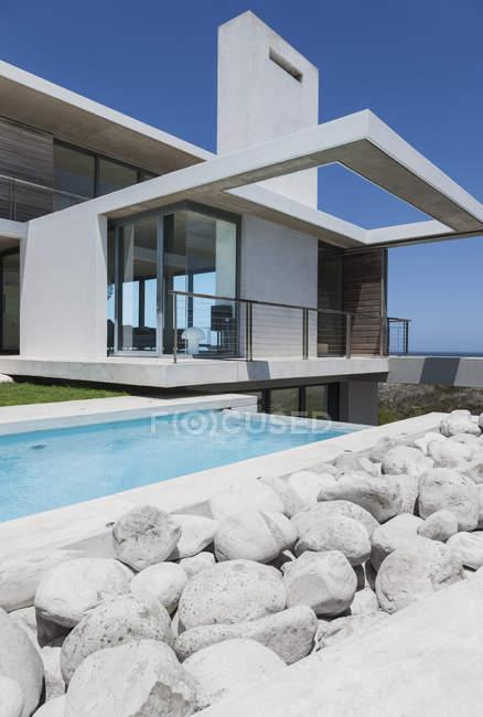 Rocce e piscina fuori casa moderna — Foto stock