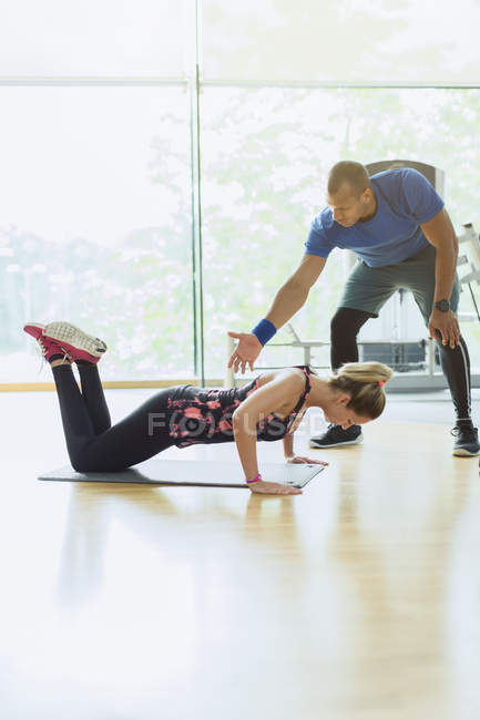 Personal trainer guiding woman doing push-ups on knees at gym — Stock Photo