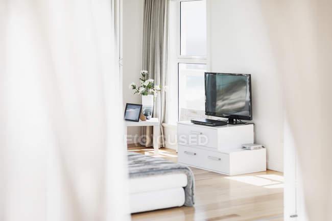 Телевизор и диван в солнечной гостиной — стоковое фото