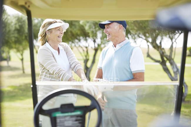 Casal sênior rindo no campo de golfe — Fotografia de Stock