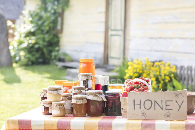 Fresh jars of honey at farmers market stall — Stock Photo