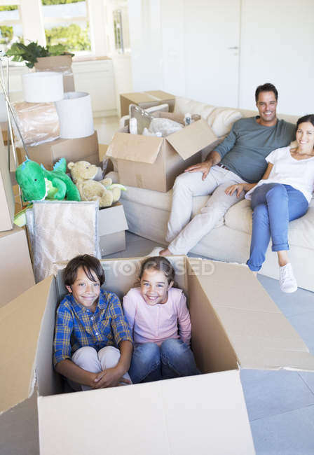 Brother and sister inside cardboard box in living room — Stock Photo