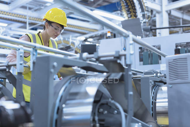 Worker at machinery in factory — Stock Photo