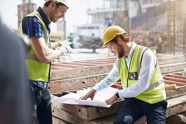 Construction worker and engineer reviewing blueprints at construction site — Stock Photo