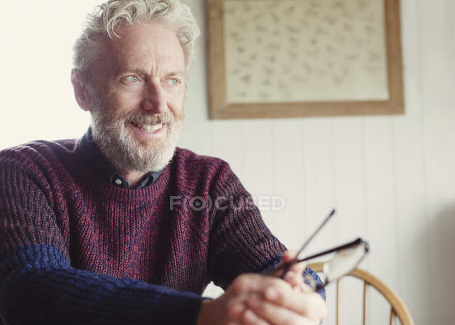 Pensive senior man holding eyeglasses and looking away — Stock Photo