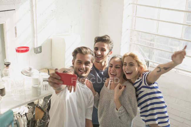 Enthusiastic young adult roommates taking selfie in kitchen — Stockfoto