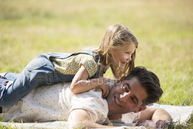 Verspielte Tochter Verlegung auf Vaters im sonnigen Bereich — Stockfoto