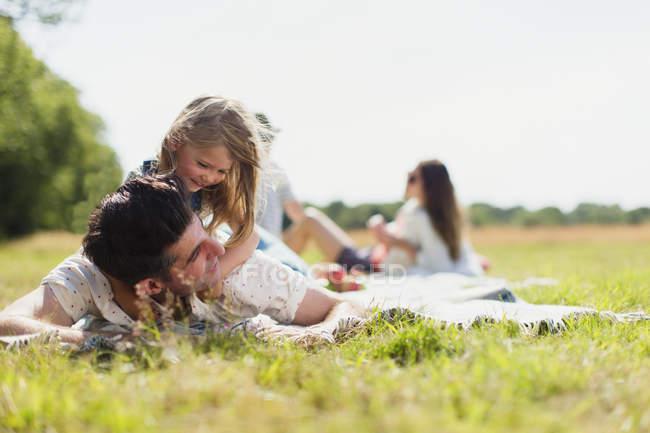 Ласковая дочь лежит на вершине отца в солнечном поле — стоковое фото