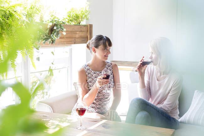 Women drinking wine and talking on cafe sofa — Stockfoto