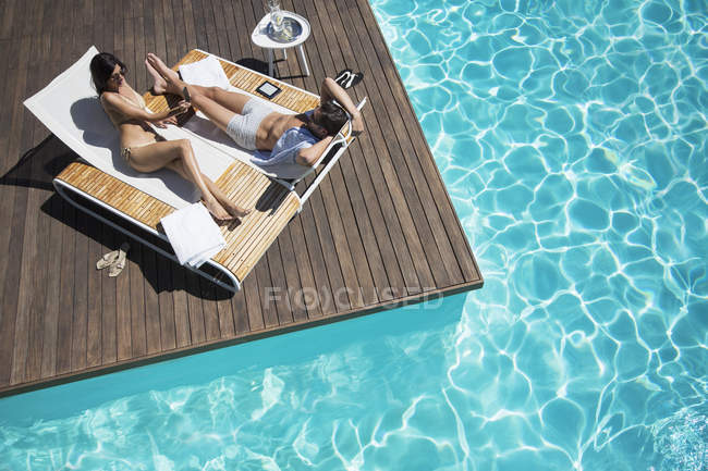 Couple laying on lounge chair at poolside — Stock Photo