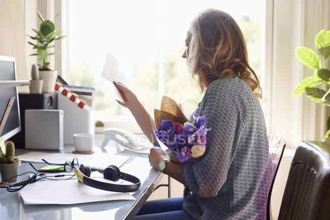 Frau erhält Blumenstrauß und Lesekarte im Home Office — Stockfoto