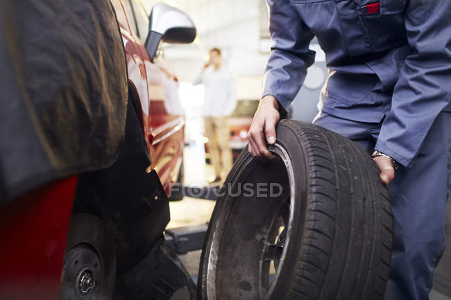 Mechanic replacing tire in auto repair shop — Stock Photo