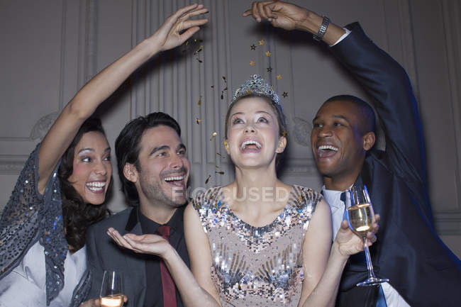 Friends reaching over happy woman wearing tiara — Stock Photo
