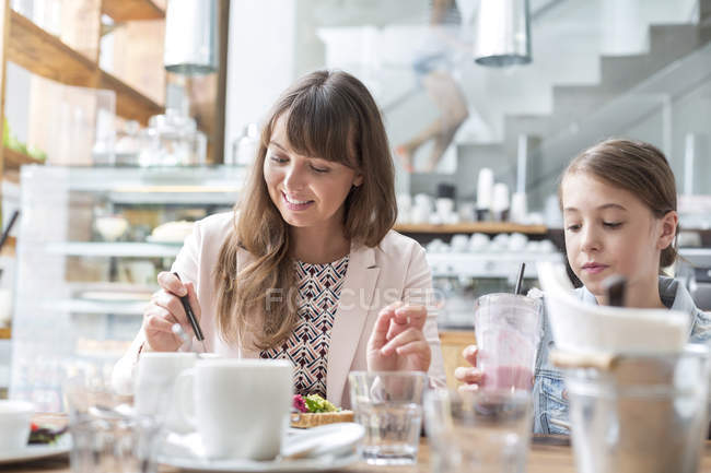 Mutter und Tochter essen und trinken am Café-Tisch — Stockfoto