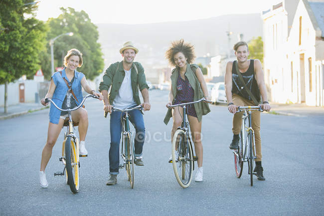 Portrait smiling friends sitting on bicycles on road — Stock Photo