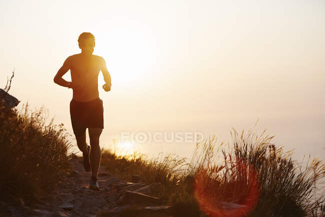 Silhouette of man running on trail with sunset ocean in background — Stockfoto