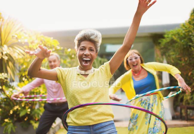 Портрет грайливий зрілі дорослі спінінг з пластикових обручі в саду — стокове фото