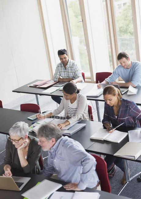 Étudiants qui étudient en salle de classe de l'éducation des adultes — Photo de stock