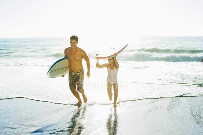 Vater und Tochter tragen Surfbrett und Bodyboard am Strand — Stockfoto