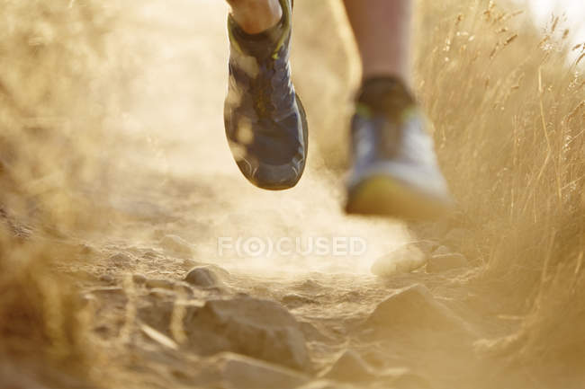 Close up of runner?s feet on dirt trail — Stockfoto