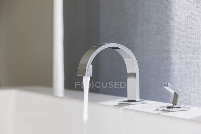 Closeup of water emitting from modern faucet — Stock Photo