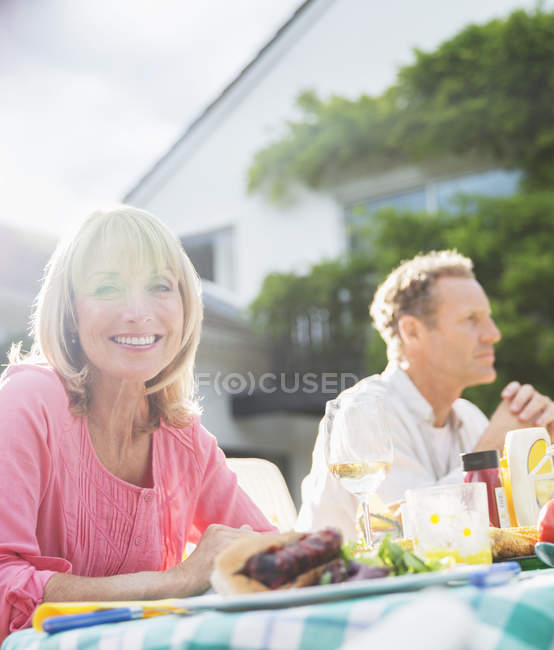 Happy smiling woman at table in backyard — Stock Photo