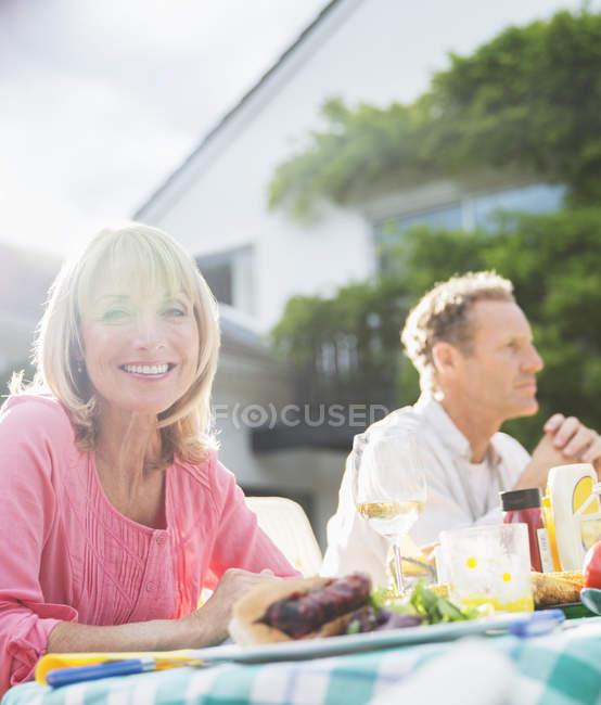 Щасливі усміхається жінка за столом у дворі — стокове фото