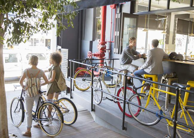 Personnes avec des vélos dans un café urbain en plein air — Photo de stock