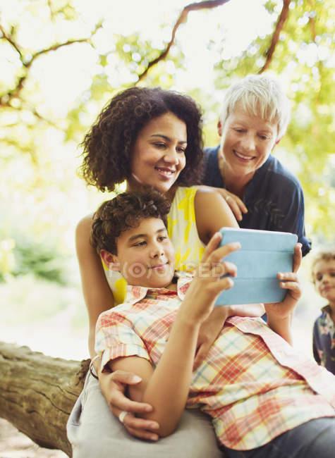 Famille multi-génération utilisant une tablette numérique à l'extérieur — Photo de stock