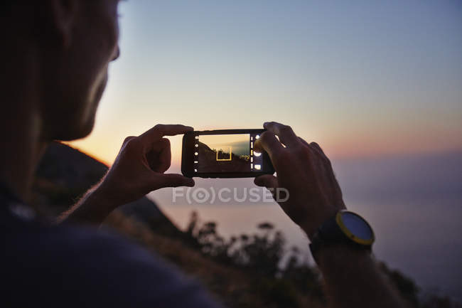 Man photographing sunset ocean view with camera phone — Stockfoto