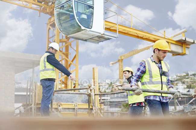 Foreman guiding construction workers below crane at construction site — Stock Photo