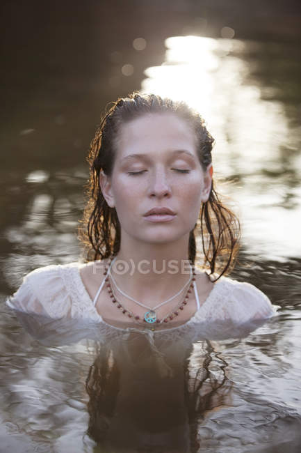Serene woman with eyes closed in river — Stock Photo