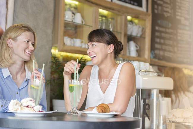 Women talking and drinking at cafe table — Stockfoto