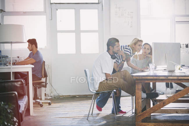 Young creative business people working at computer in sunny office — Stockfoto