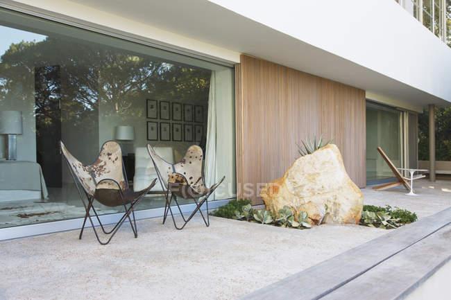 Стулья и валун на патио современного дома — стоковое фото