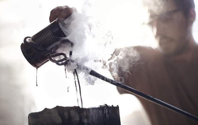 Schmied Gießen dampfende Flüssigkeit über Schmiedeeisen — Stockfoto
