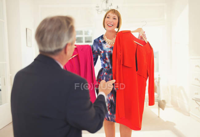 Husband helping wife decide which dress to wear — Stockfoto