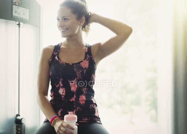Lächelnde Frau mit Flasche Wasser ruht in Turnhalle — Stockfoto