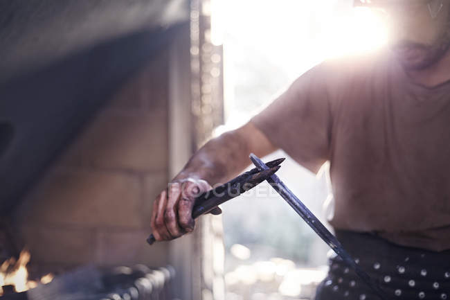 Blacksmith shaping tool with pliers in forge — Stock Photo