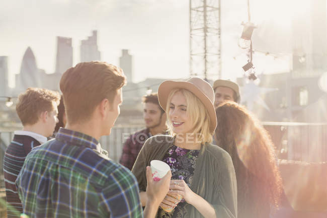 Young man and woman drinking and talking at rooftop party — Stockfoto