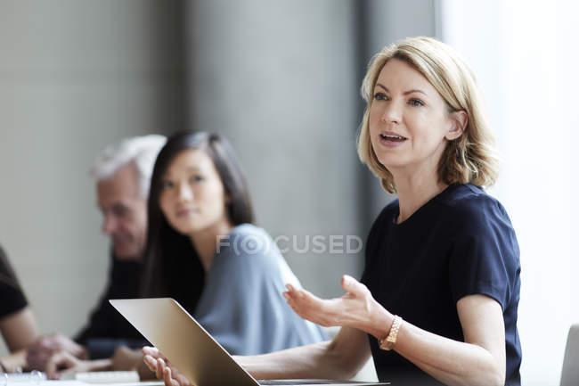 Empresária gesticulando e conversando em reunião — Fotografia de Stock