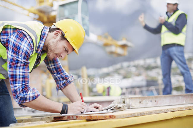 Construction worker writing on clipboard at construction site — Stock Photo